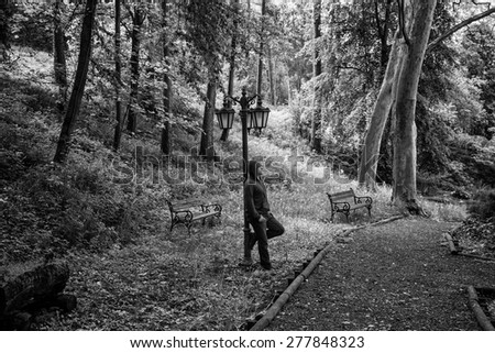 Black and white photo of a young man leaning against an old street lamp in a park. Concept for grief or sadness - stock photo