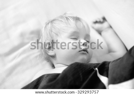 Black and white photo of adorable toddler boy sleeping in a bed - stock photo
