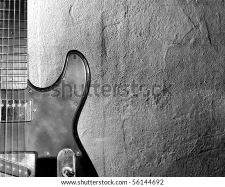 Black and white photo of an elertric guitar near wall - stock photo