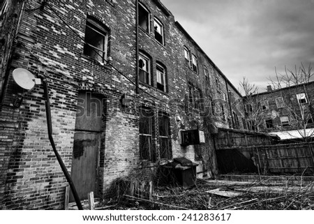Black and white photo of an old run down brick building in an urban setting. Sadly these are seen frequently in American cites. - stock photo