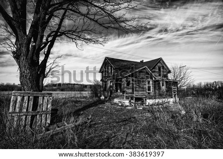 Black and white photo of an old scary abandoned farm house that is deteriorating with time and neglect. - stock photo