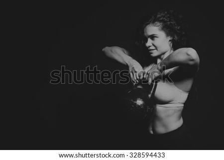 Black and white photo of beautiful athlete on a dark background. Women's fitness. Working with dumbbells. Photos for sporting magazines, posters and websites. - stock photo
