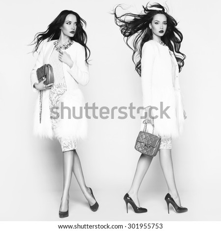 Black and white photo of beautiful brunette model in fashion clothes posing in studio. Wearing coat, handbag, shoes - stock photo