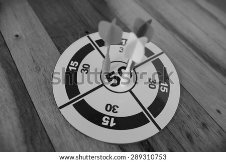 Black and white photo of darts isolated on a wood background - stock photo