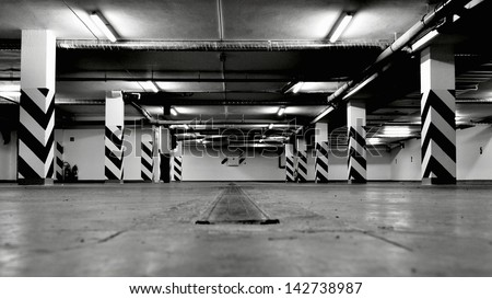 Black and white photo of empty underground parking garage. Shot in wide angle. - stock photo