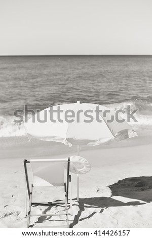 Black and white photo of female hat, chair and umbrella on stunning tropical beach vacation background - stock photo
