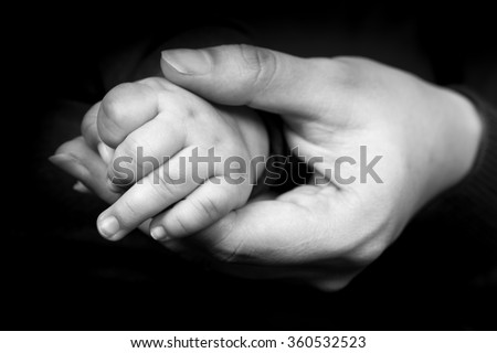 Black and white photo of hand of mother holding heir baby's small - stock photo