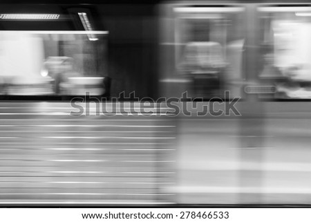 Black And White Photo Of Moving Train In Subway Station - stock photo