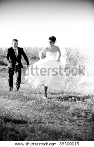 Black and white photo of newly married couple chasing in field - stock photo