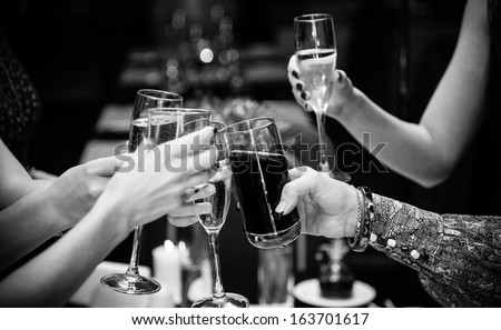 Black and white  photo of people holding glasses of wine and clinking - stock photo