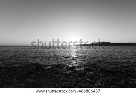 Black and white photo of sunrise on the horizon behind sea at Malta, St. Paul - stock photo