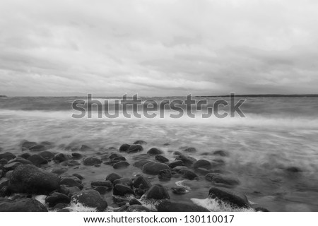 Black and white photo of the Baltic ocean a cloudy rainy day, Ekerum, Sweden - stock photo