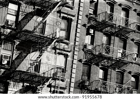 Black and white photo of the exterior of a building in New York with old fire escape. - stock photo