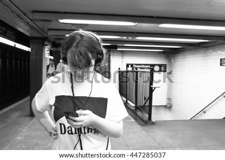 Black and white photo of tween/teen girl in New York city subway waiting for train and listening to music with smartphone and headphones.  Selective focus. Candid photo.  - stock photo