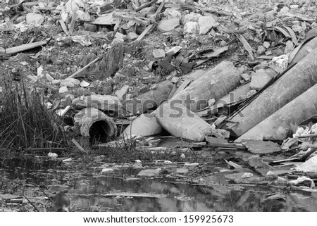 black and white photo of waste pipe or drainage polluting environment, concrete pipe. - stock photo