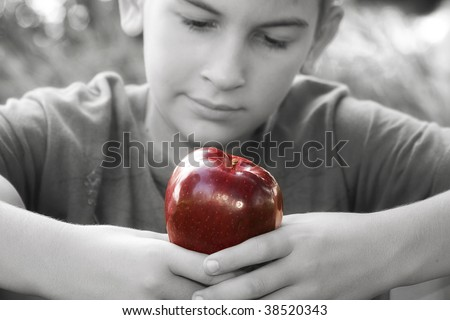 Black and white photo of young boy admiring the red apple about to eat - stock photo