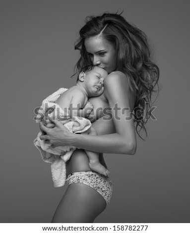 Black and white photo of young mother kissing baby - stock photo