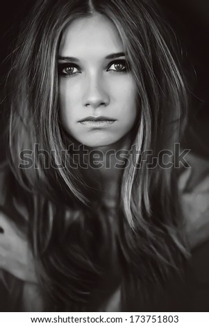 Black and white photo portrait of a girl who looks at the camera. - stock photo