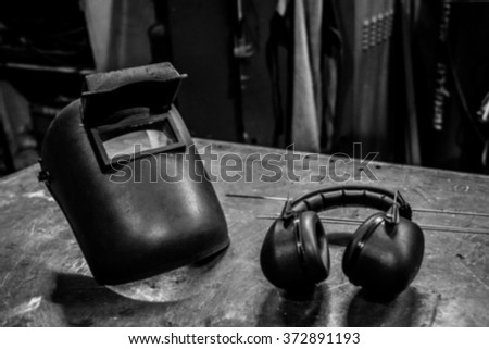 black and white photo style and blurred background of Night scene  industrial  welding mask and safety headphone on steel table in factory  - stock photo