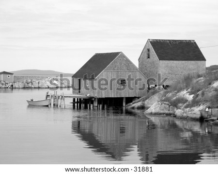 Black and white photograph of old fishing shacks. - stock photo