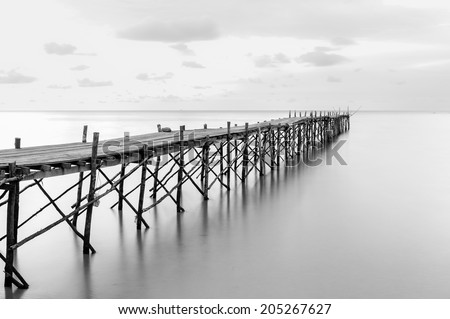 Black and white photography of a beach wooden pier - stock photo