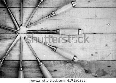 Black and white photography of chisel set arranged in circle over wooden background. Top view, closeup flat lay photo - stock photo