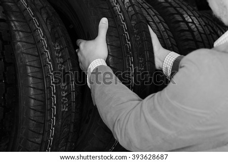 Black and white photography of person hands choosing a car tire. closeup - stock photo