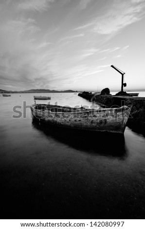 black and white photography of sky and sea at sunset with a little old fishing boat in the Mar Menor, Spain - stock photo