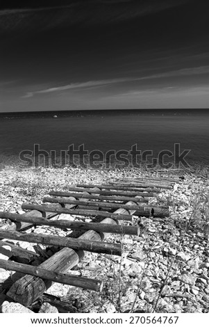 black and white photography. sea and the horizon and the sand and rocks and stairs - stock photo