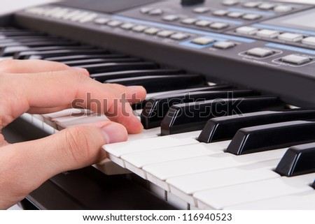 Black and white piano keys and hand fingers pressing the keys. - stock photo