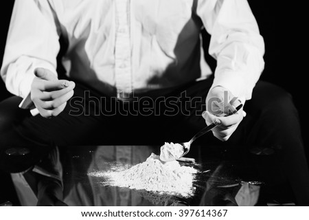 Black and white picture of a man preparing cocaine  - stock photo