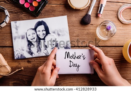Black-and-white picture of mother hugging her daughters and various make up products. Hands of unrecognizable woman holding Mothers Day card. Studio shot on wooden background. - stock photo