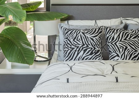 black and white pillows and blanket on modern bed at home - stock photo