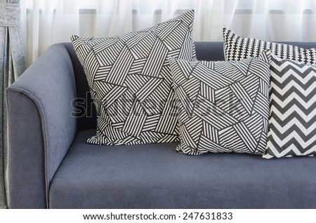 black and white pillows on blue sofa in living room at home - stock photo