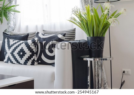 black and white pillows on white sofa with vase of plant in living room - stock photo