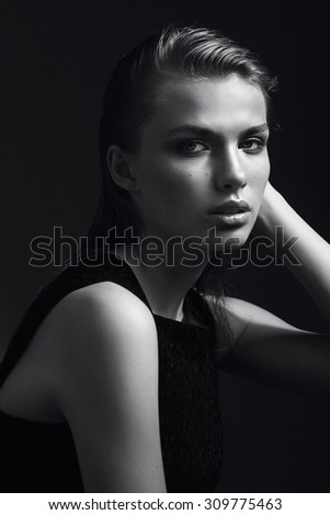 Black and white portrait of a beautiful girl in the studio on a black background - stock photo