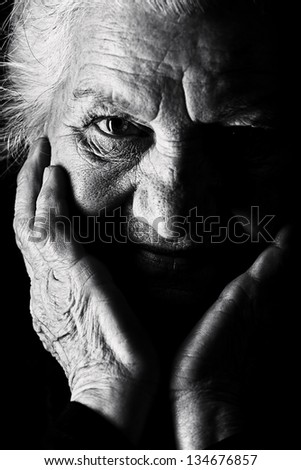 Black-and-white portrait of a calm senior woman looking at the camera. Over black background. - stock photo