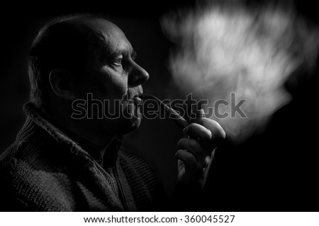 Black and white portrait of a caucasian man smoking tobacco pipe - stock photo