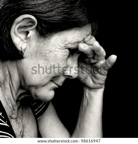 Black and white portrait of a depressed old  woman suffering from stress or a strong headache isolated on black - stock photo