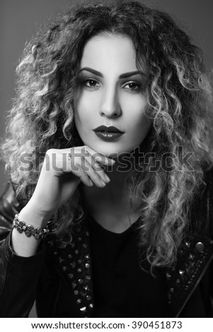 black-and-white portrait of a gorgeous  woman with curly hair in the style of glam rock - stock photo