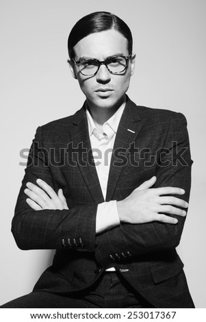 Black and white portrait of a handsome man with glasses and a suit in the studio on a white background, the concept of fashion - stock photo
