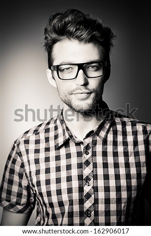 Black-and-white portrait of a handsome young man in spectacles. - stock photo