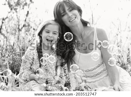 Black and white portrait of a mother and daughter relaxing on holiday, with their heads together joyfully smiling looking at floating bubbles in a spring field. Family activities lifestyle, outdoors. - stock photo