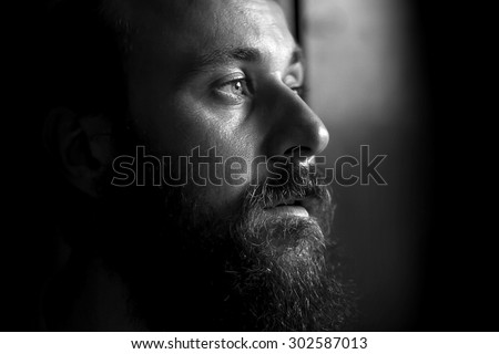 Black and white portrait of a serious man, side view - stock photo
