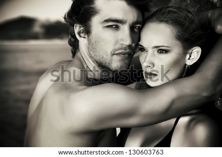 Black-and-white portrait of a sexual young couple in love having holidays on the sea. - stock photo