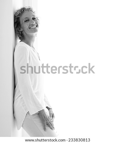 Black and white portrait of a smart professional business woman smiling and leaning on a wall by a glass door with sunny light, aspirational lifestyle. Home interior with business woman standing. - stock photo