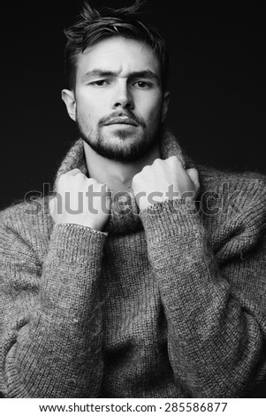 Black and white portrait of a stylish young man in a warm pullover in the studio - stock photo