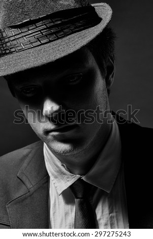 Black and white portrait of a young man in a hat, suit and tie - stock photo