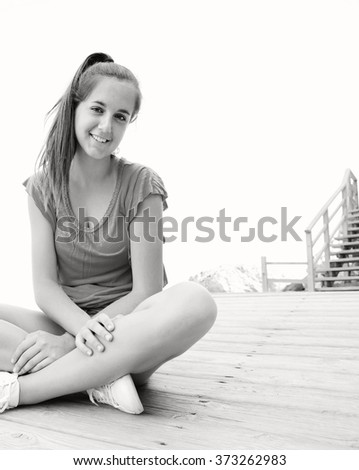Black and white portrait of adolescent girl sitting on wooden deck by the sea, smiling on a summer holiday against sky, outdoors. Teenager young woman travel lifestyle, healthy recreation, relaxing.  - stock photo
