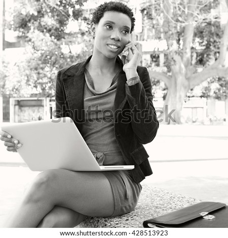 Black and white portrait of african american business woman sitting in city, with laptop computer, smart phone call conversation, smiling outdoors. Professional woman using technology, lifestyle. - stock photo